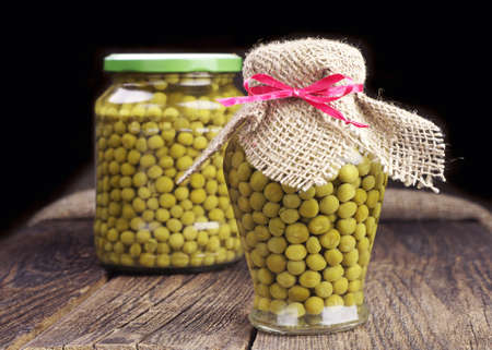 canned peas: Canned green peas in glass jar on wooden table