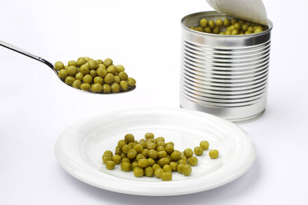 canned peas: Canned peas in spoon and plate on white background