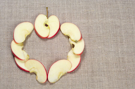 Sliced red apple in the shape of heart on background fabric photo