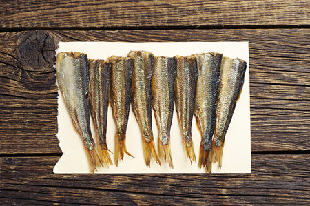 sprats: Fresh smoked sprats on a paper on vintage wooden board