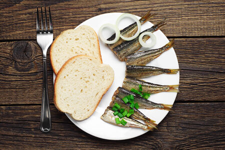 Smoked sprats and bread on table photo