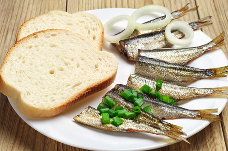 sprats: Smoked sprats and bread on a white plate Stock Photo