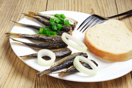 sprats: Fresh smoked sprats and white bread on table. Selective focus Stock Photo