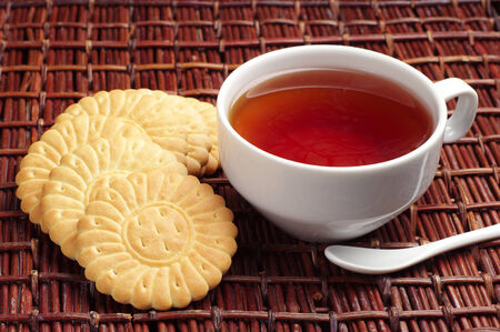 Cup of tea and cookies on wicker wooden table photo