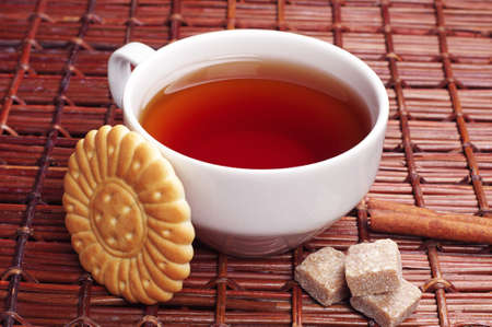 Cup of tea with biscuits on wicker wooden table photo