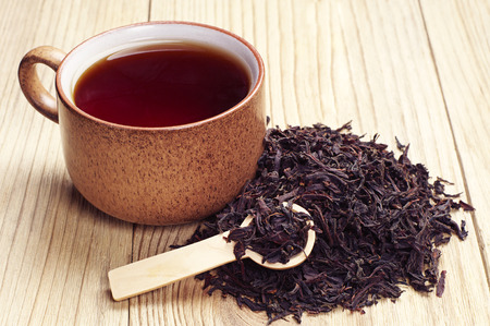 tea spoon: Black tea in a cup and dried leaves on wooden background Stock Photo