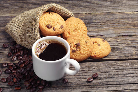 Cup of coffee and cookies in sack on vintage wooden table. Top view photo