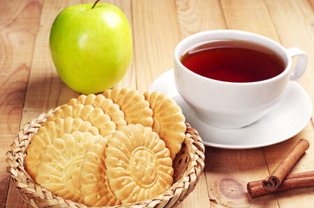 Cup of tea with cookies and green apple on wooden table photo