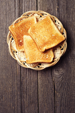 Toast bread in a wicker plate on vintage wooden background. With place for text. Stock Photo