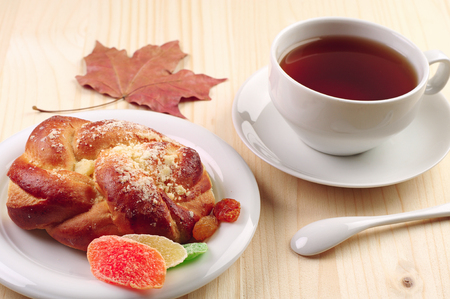 Cup of tea and bun with dried fruit on wooden table Stock Photo