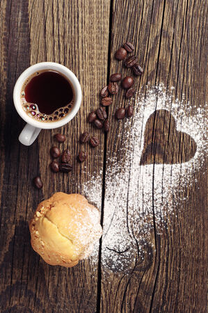 Cup of coffee and cupcake on vintage wooden background with heart   photo