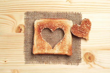 Slice of toast bread with cut out heart shape on wooden table photo