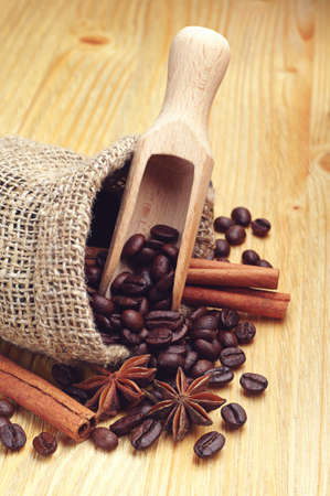 Coffee beans, cinnamon and anise with spoon on wooden background photo