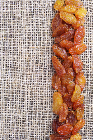 Raisins on burlap background closeup photo