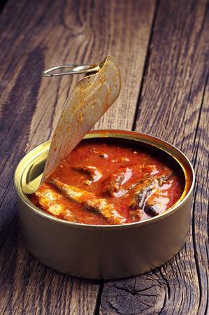 sprat: Sprat in tomato sauce on vintage wooden background
