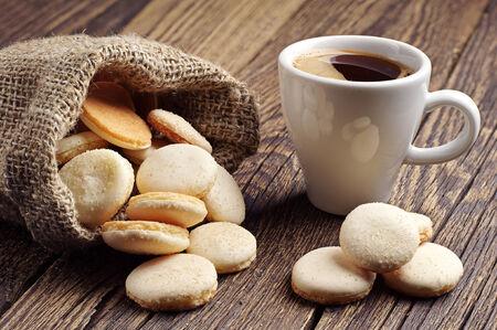 Kopje koffie en kleine ronde koekjes in zak op vintage houten tafel
