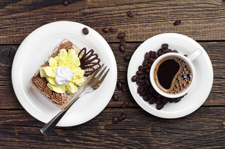 Cake and cup of coffee on wooden table viewed from above photo