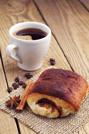 Delicious bun with cinnamon and cup of hot coffee