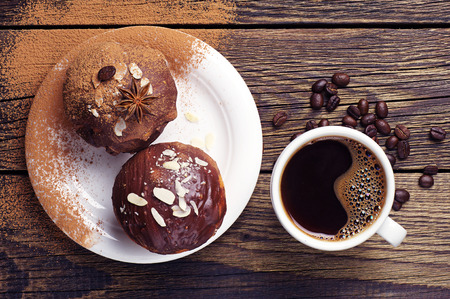 Top view of a cup of coffee and cupcake with chocolate and nuts on wooden table