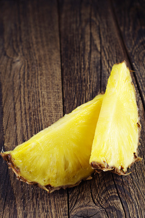 Ripe pineapple slices on vintage wooden background