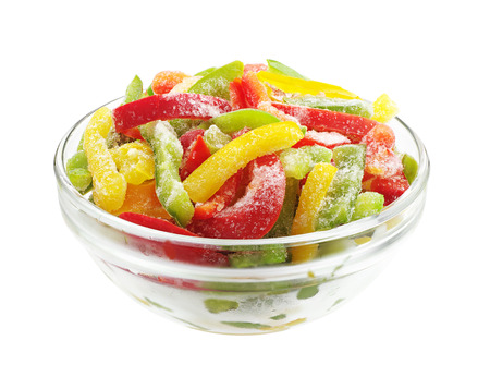 Frozen multicolored peppers slices in glass bowl isolated on white background photo