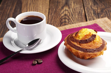 Cup of hot coffee and cupcake with chocolate on wooden table photo