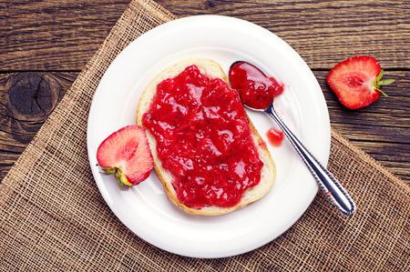 Bovenaanzicht op brood met aardbeien jam op houten tafel