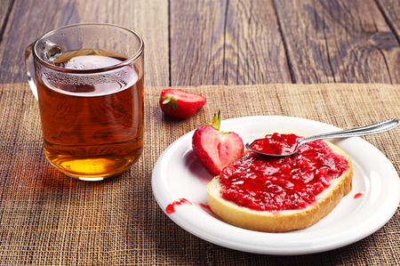 White bread with strawberry jam and cup of tea on wooden table Stok Fotoğraf