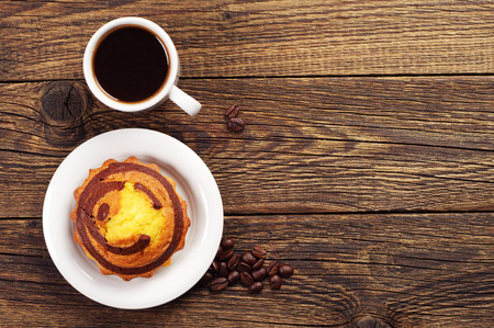 wooden table top view: Sweet cupcake with chocolate and cup of coffee on wooden table. Top view