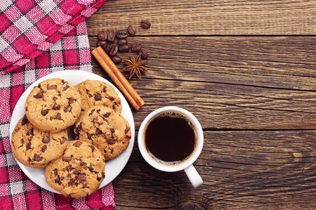 Bovenaanzicht op kopje koffie en plaat met chocolade koekjes Stockfoto
