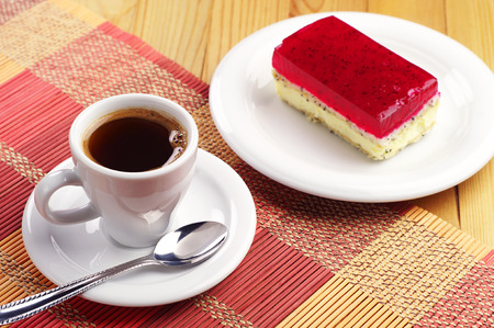 Cup of coffee and strawberry cake with poppy on colorful bamboo napkin
