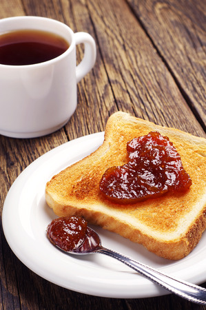 Toast bread with jam in shape of hearts and cup of tea on wooden table photo