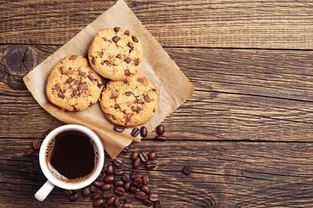 Top view on wooden background with coffee and chocolate cookies  Stok Fotoğraf