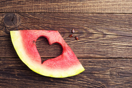 Slices of watermelon with cut in the shape of heart on wooden background. Top view