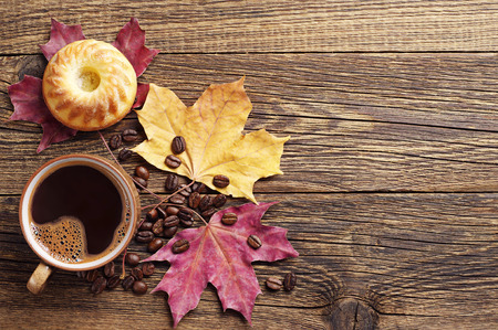 wooden table top view: Cup of coffee with cupcake and autumn leaves on vintage wooden table. Top view