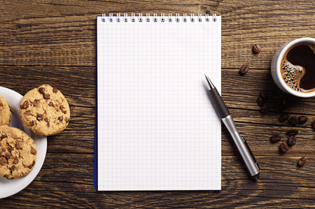 Opened notepad and cup of coffee with chocolate cookies on vintage wooden table. Top view photo