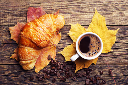 Croissant, cup of hot coffee and autumn leaves on wooden background. Top view