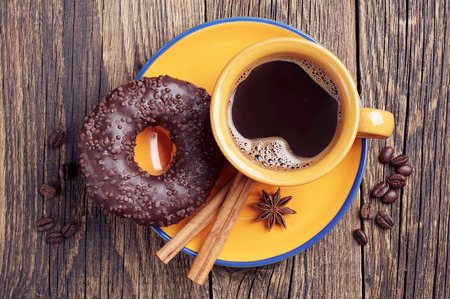 Cup of hot coffee and chocolate donut on vintage wooden background. Top view