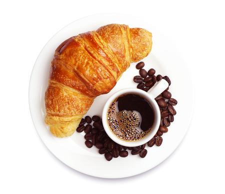 白い背景の上のホット コーヒーのカップを持つ新鮮なクロワッサン