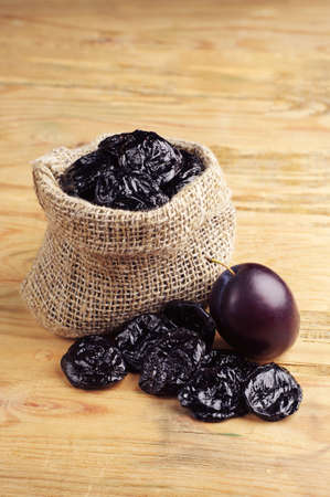 Prunes in sack on vintage wooden background photo