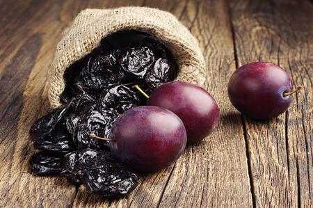 Prunes with plums in small sack on old wooden table