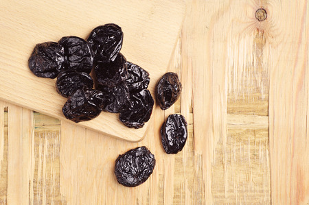 Prunes on wooden table closeup. Top view