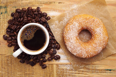 wooden table top view: Donut with sugar and cup of hot coffee on wooden table. Top view