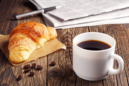 Cup of coffee, croissant and newspaper on wooden table photo