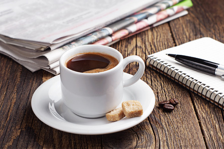 Cup of coffee, newspaper and notepad on old wooden table