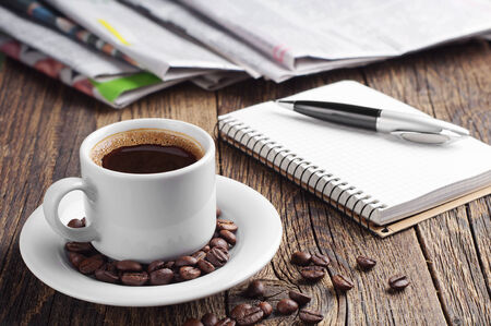 Cup of coffee, newspaper, notepad and pen on old wooden table photo