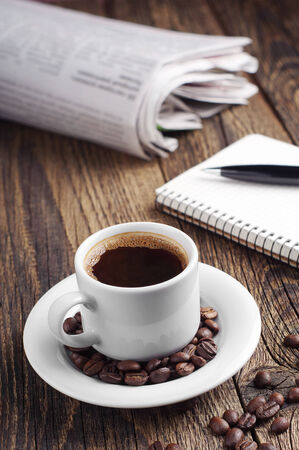 Coffee cup and newspaper on vintage wooden table photo