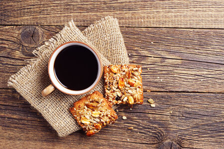 wooden table top view: Coffee cup and cookies with nuts on vintage wooden table. Top view
