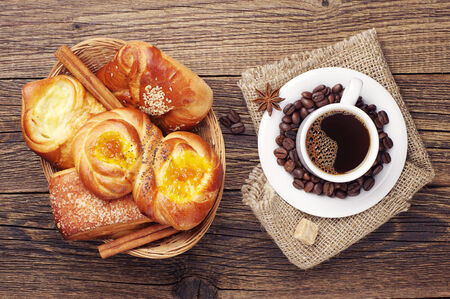 Coffee cup and sweet buns in wicker basket on old wooden table. Top view photo