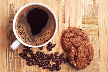 Cup of hot coffee and chocolate cookies with nuts on old wooden table. Top view
